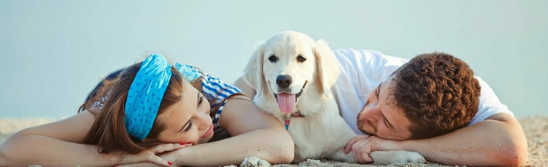 White dog laying between male and female on the beach
